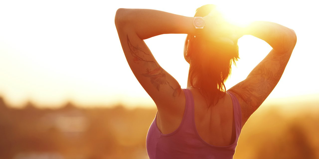 Fit and healthy young woman at sunset